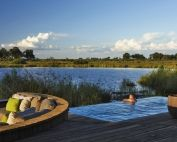 Kings Pool Camp overlooks Kings Pool Lagoon in the Linyanti Wildlife Reserve. Relax at the pool deck and spot elephant crossing the channel, Botswana, Wilderness Safaris.