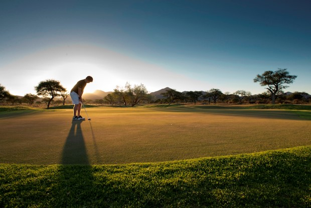 A golfer lining up a put as the sun goes down. Image by Omeya Golf and Residential Oasis, Golf Courses of Namibia