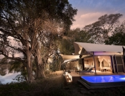 Thorntree River Lodge exterior by night ©African Bush Camps